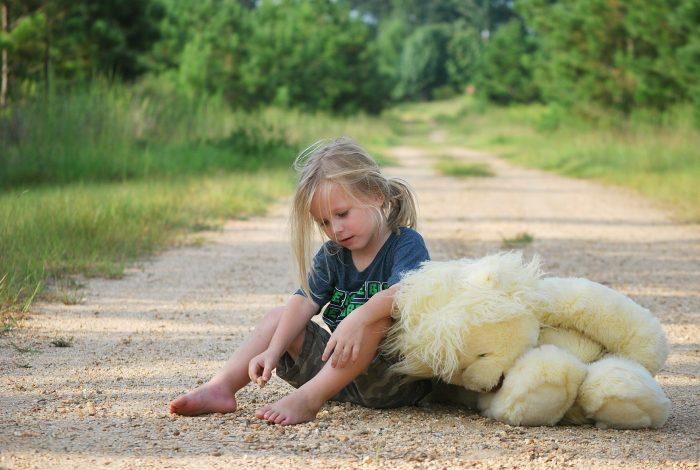 Mädchen_sitzt auf Waldweg